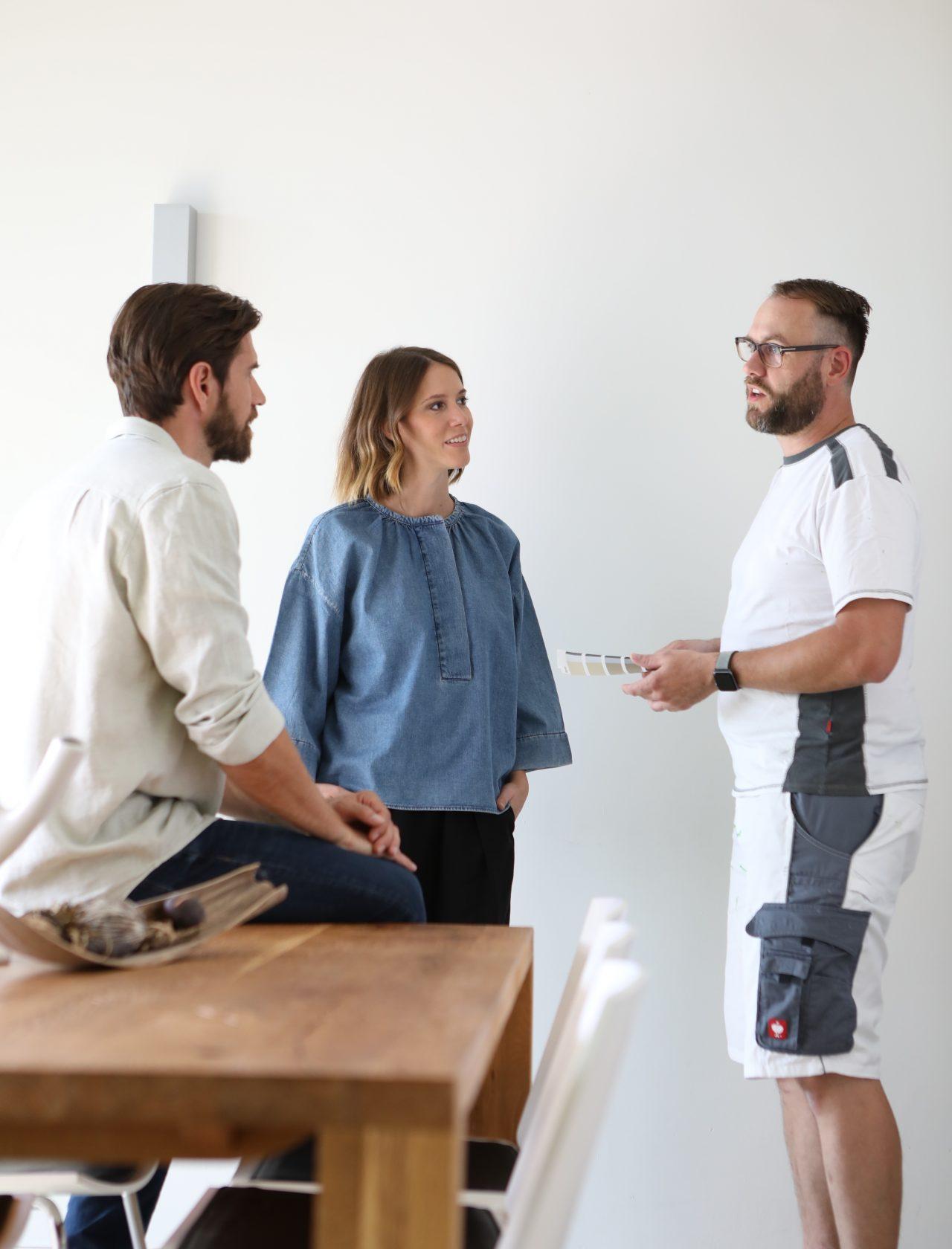 Malermeister spricht mit Mann und Frau zu Wandfarbe