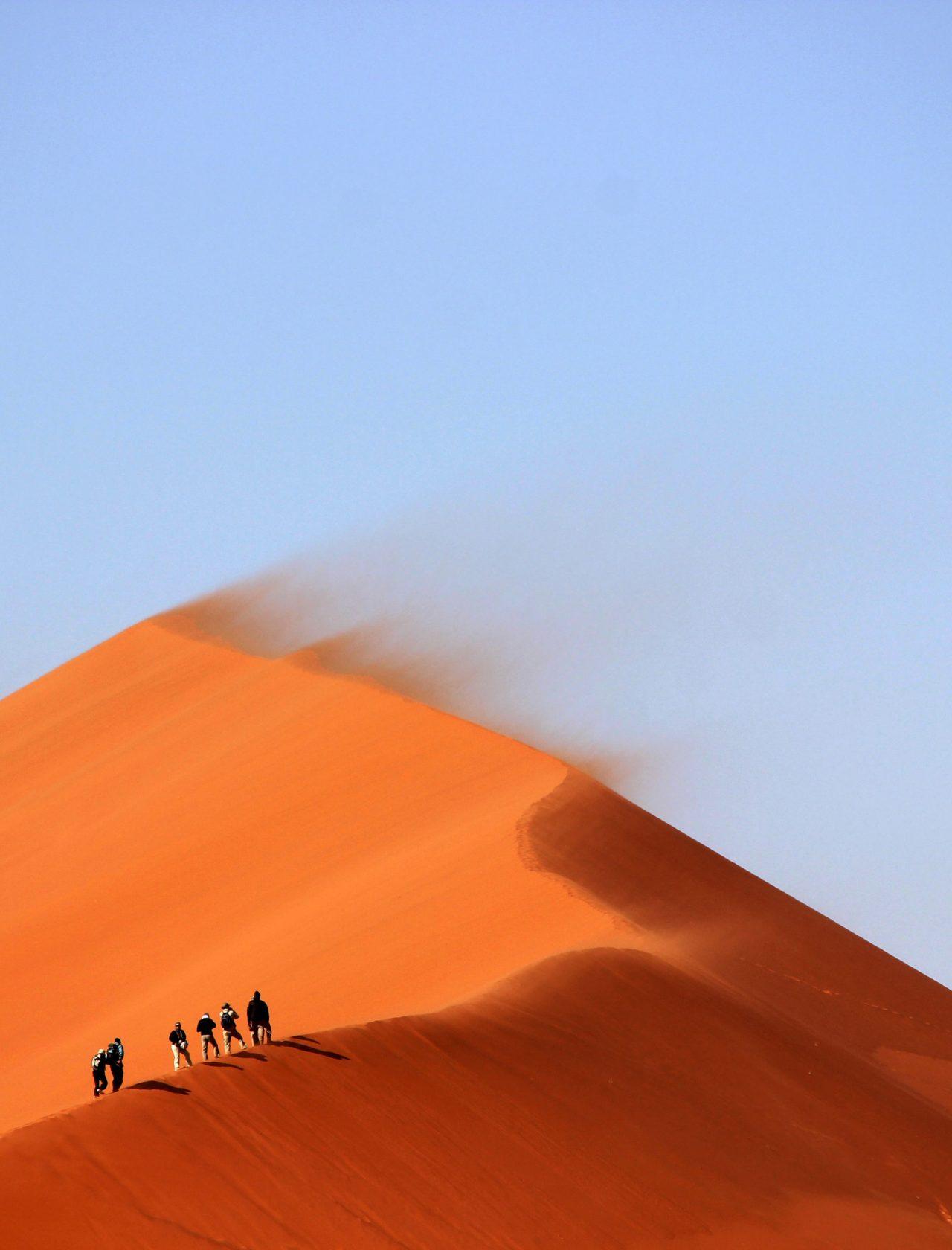 Orange Düne, auf der Menschengruppe läuft, vor blauem Himmel