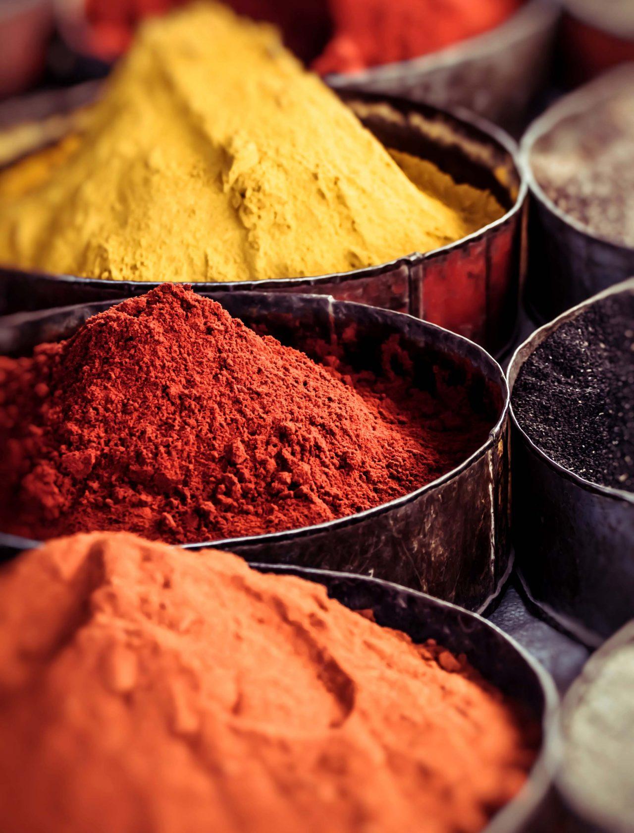 Verschiedene Farbpulver aufgehäuft in großen Behältern