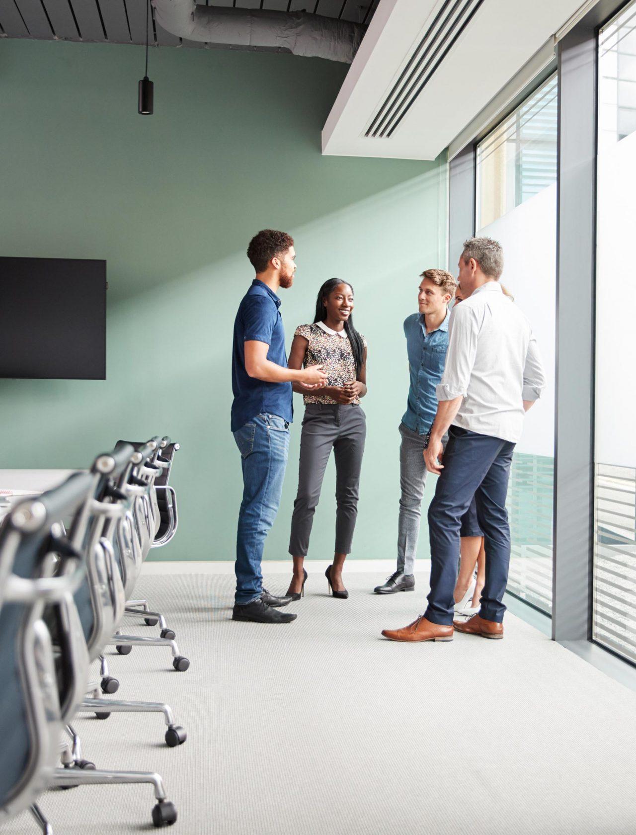 Eine Gruppe von Menschen steht in einem Meetingraum mit grüner Wand