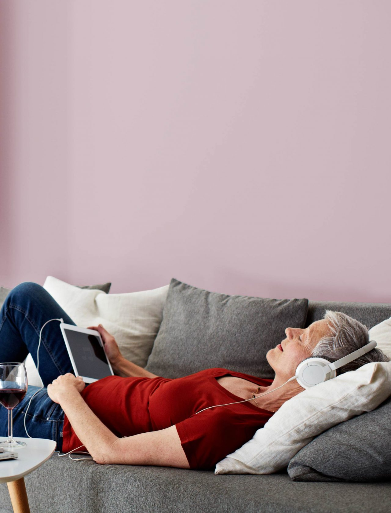 Frau liegt mit Kopfhörern auf einem Sofa, hellrote Wand, Tisch, Balkontür mit Fensterladen