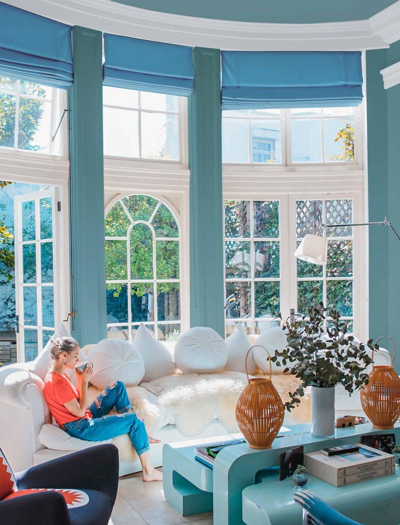Frau mit Kaffeetasse sitzt entspannt auf einem Sofa, blaues Sideboard und Sessel