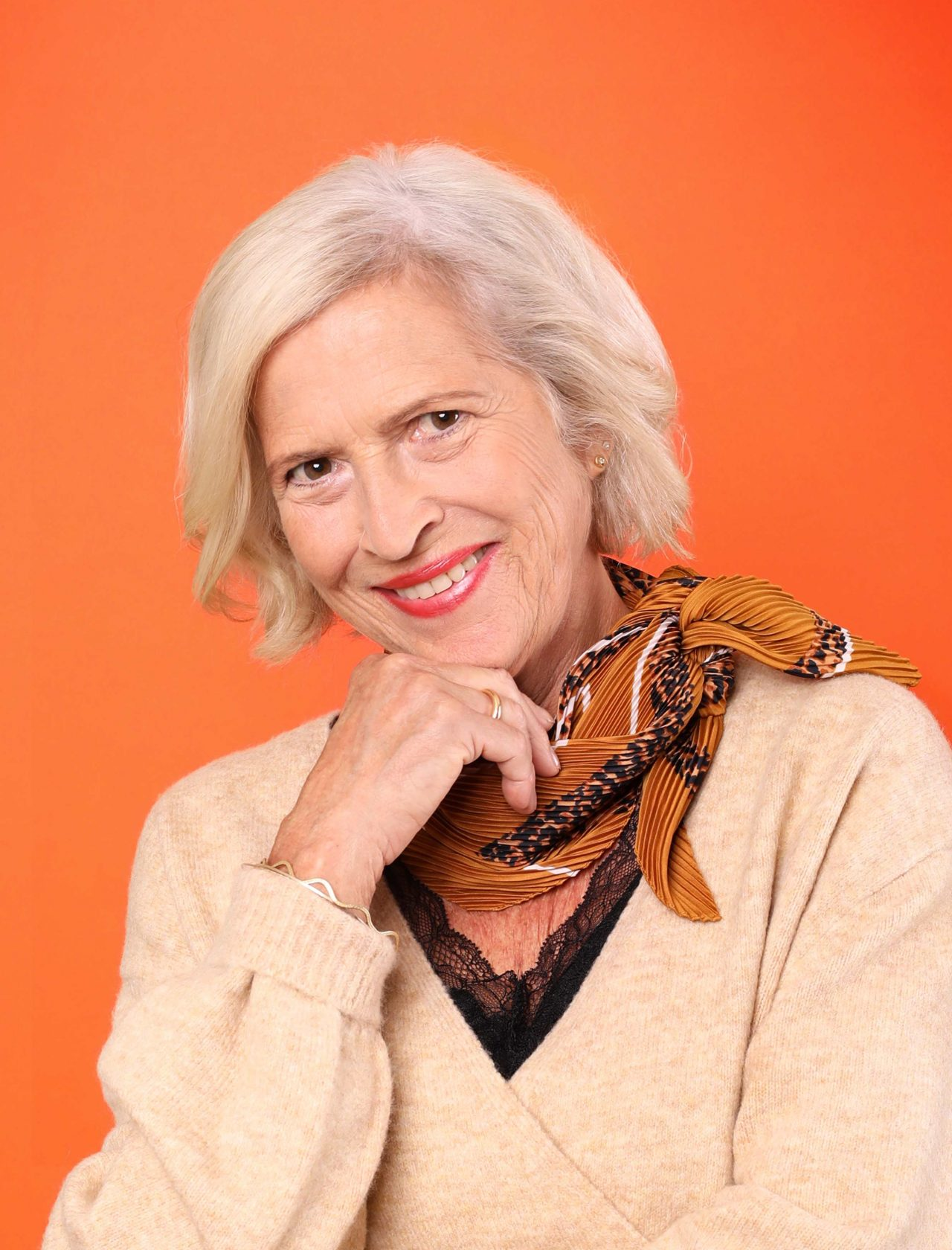 Ältere Frau vor oranger Wand