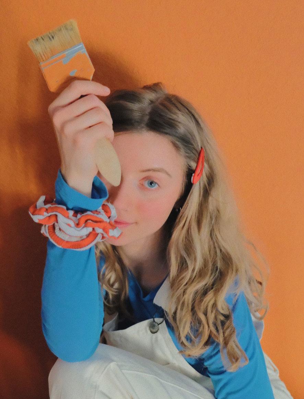 Nanda Weskott vor oranger Wand mit Pinsel in der Hand
