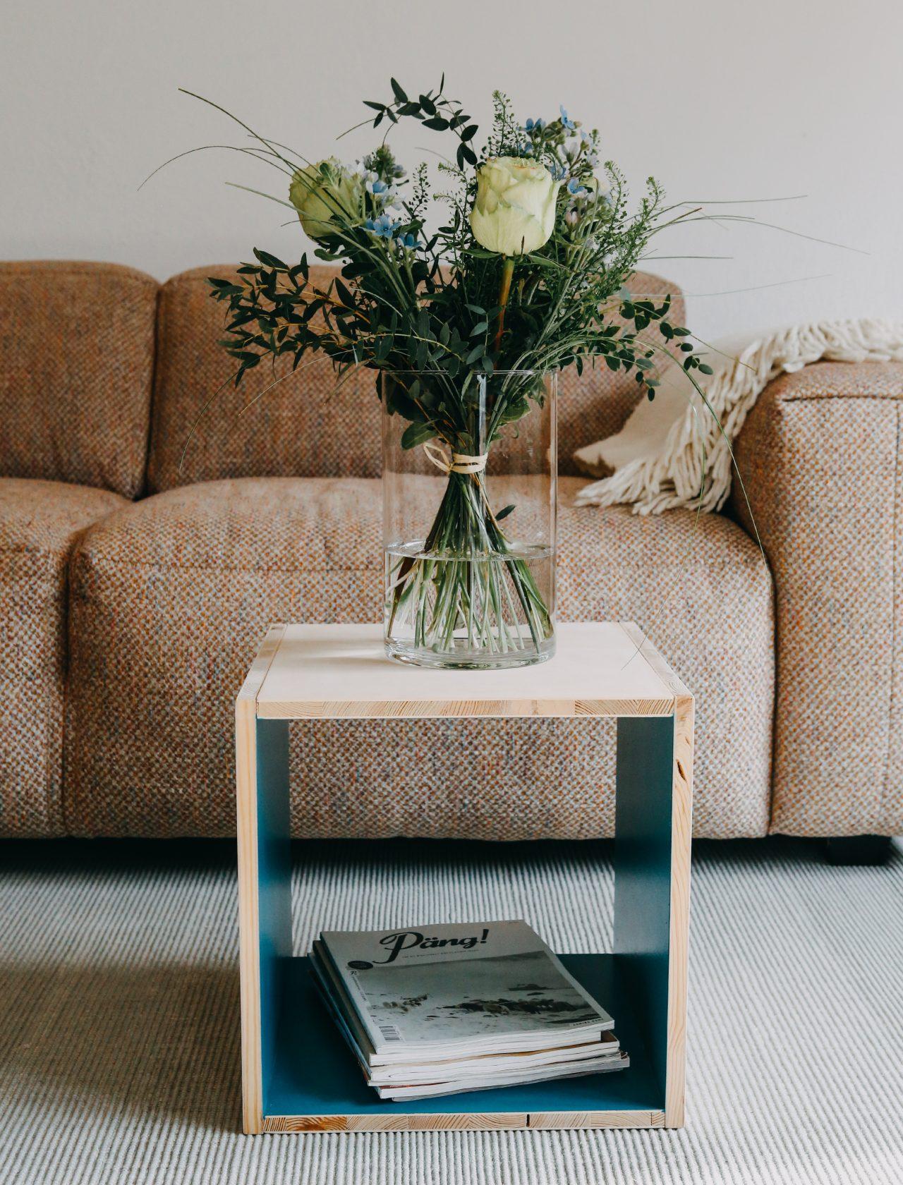 Türkiser Beistelltisch mit Blumenstrauß vor Sofa