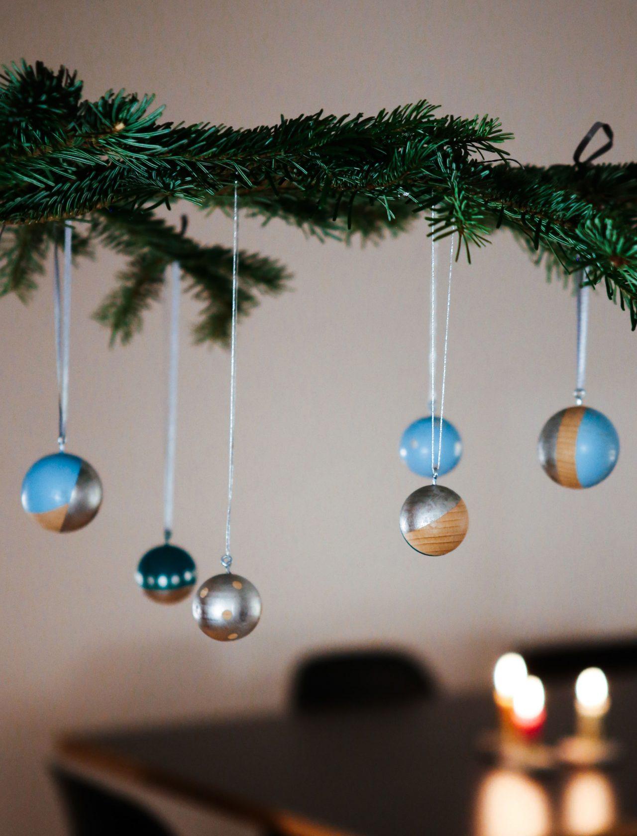 Bunte Weihnachtskugeln hängen an einem Tannenzweig