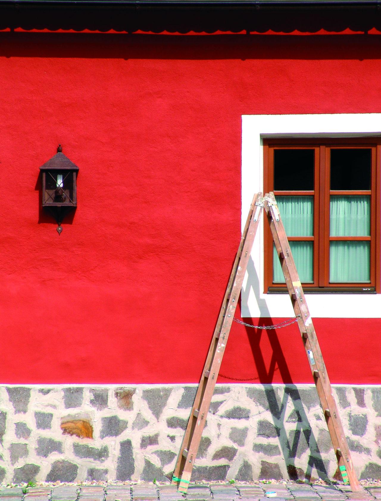 Leiter steht vor rotem Haus und Fenster