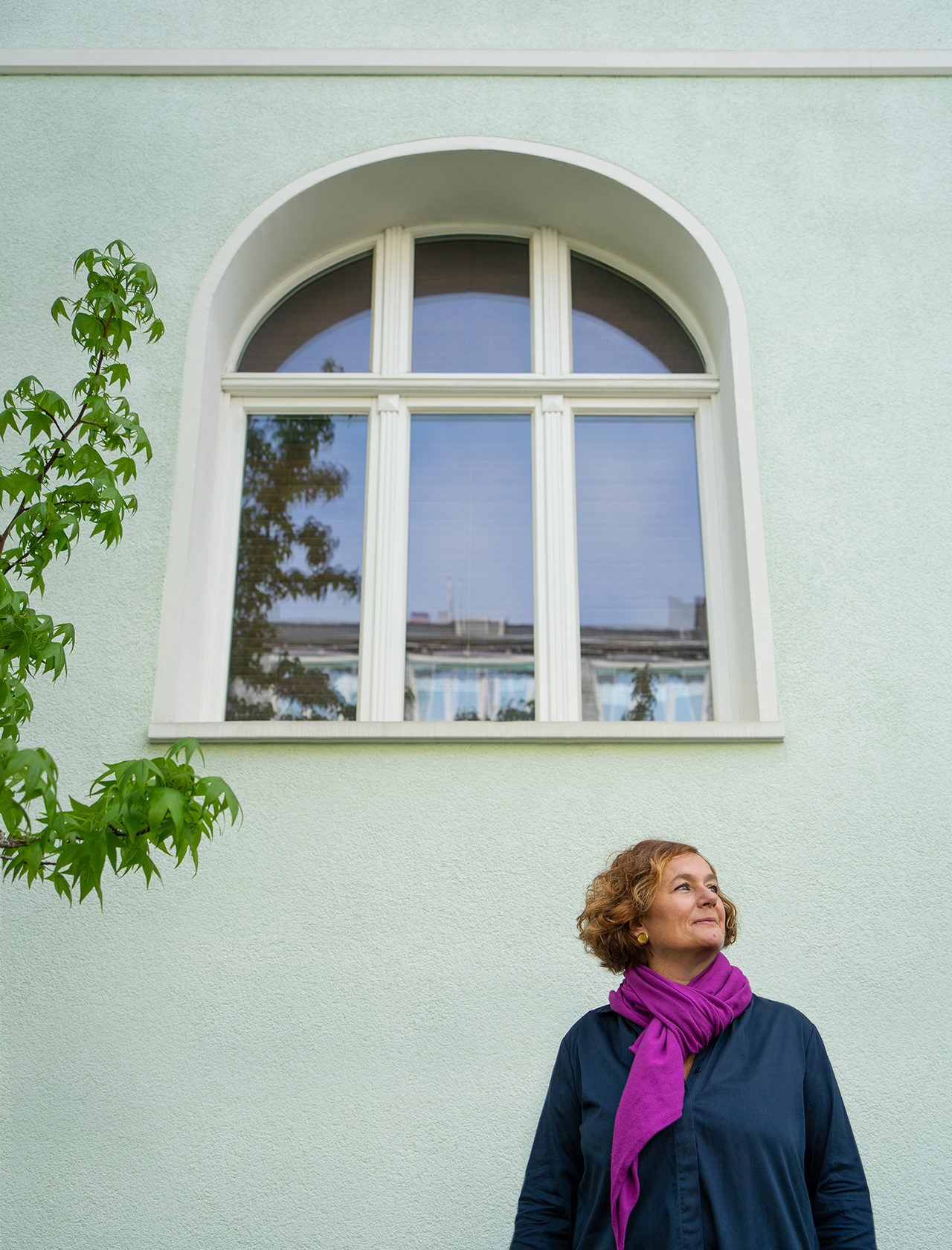 Frau steht vor grün gestrichenem Gründerzeithaus